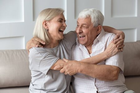 Photo pour Happy mature husband and wife sit on comfortable couch have fun laughing enjoying weekend together, funny overjoyed optimistic senior spouses cuddle hug on sofa at home, elderly humor concept - image libre de droit