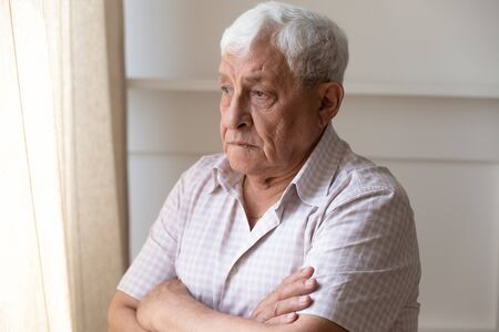Photo pour Upset old man look in window distance feel lonely and distressed thinking missing past days, thoughtful upset mature male lost in thoughts mourning yearning, remembering, elderly solitude concept - image libre de droit