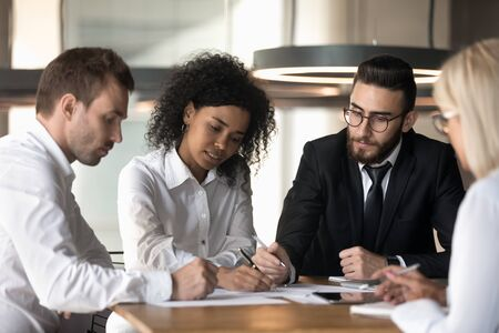 Foto für Multiracial team sitting reviewing documents financial stats, african woman boss teach staff explain project papers at group meeting, enterprise employees take part in briefing brainstorming concept - Lizenzfreies Bild