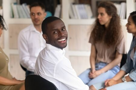 Photo pour Head shot portrait of smiling African American man sitting at group therapy session, male psychologist looking at camera, coach counselor psychotherapist posing for photo with diverse people - image libre de droit