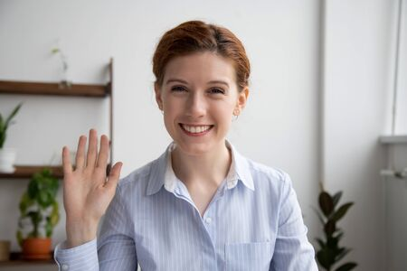 Photo pour Head shot portrait of attractive smiling businesswoman waving hand, looking at camera, making video call with webcam, greeting, business coach recording video for vlog, saying hello - image libre de droit