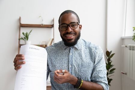 Photo pour Head shot portrait smiling African American businessman proposing to sign contract to client, looking at camera, sitting at desk, employee holding paper document in hands, pointing pen, make deal - image libre de droit