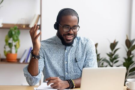 Photo for Smiling African American employee in headphones using laptop, looking at screen, making video call or watching webinar, writing notes, distance learning language concept, call center operator working - Royalty Free Image