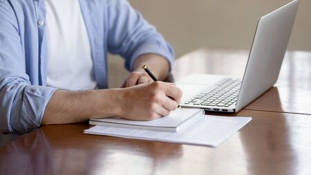 Foto für Close up of concentrated male student busy studying using laptop make notes in notebook, focused man worker employee write watching webinar or online training course on computer, education concept - Lizenzfreies Bild