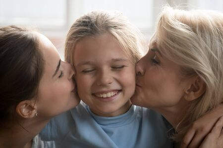 Foto de Happy millennial mother and affectionate middle aged retired grandmother kissing laughing kid girl granddaughter cheeks from both sides head shot close up portrait. Three generations bonding concept. - Imagen libre de derechos