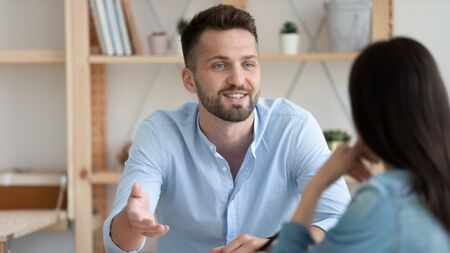 Photo pour Head shot young man involved in conversation with colleague in office. Happy coworkers chatting talking speaking, enjoying break time at workplace. Smiling job seeker introducing himself at interview. - image libre de droit