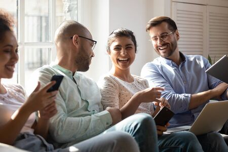 Photo pour Diverse friends gathered together spend free time with modern devices sitting on sofa having fun laughing enjoy live and virtual chat, generation addicted to gadgets, friendship, communication concept - image libre de droit