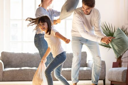 Foto de Playful young parents have fun with little preschooler daughter engaged in pillow fight in living room, happy family relax playing with small girl child, enjoy spending time at home together - Imagen libre de derechos