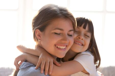 Photo pour Close up of loving young mom and little daughter hug cuddle showing care and affection, cute small girl child embrace happy mother or nanny, enjoy tender sweet moment at home together - image libre de droit