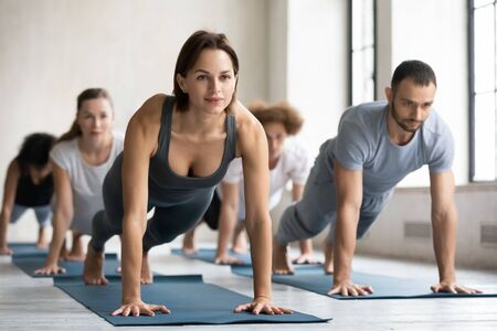 Yoga class led by caucasian woman coach training group of people performing together plank pose, do push up press up exercise strengthens spine and abdominal muscles, work out at club activity concept