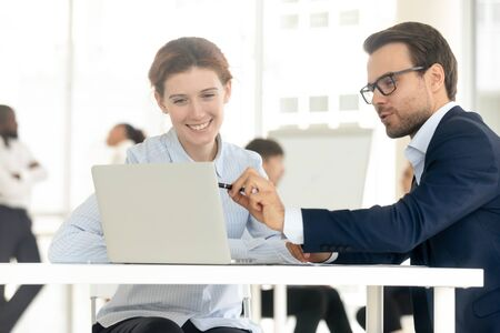 Foto de Smiling mentor coach businessman training businesswoman at personal meeting. Fun man employee consulting female client, male collegue point at laptop and presenting new project to female leader. - Imagen libre de derechos