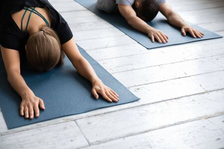 Close up image slim woman wearing sportswear lying down on mat performing Child Pose or Balasana during class, exercise stretches hips, calms brain, helps relieve stress and fatigue, wellness concept