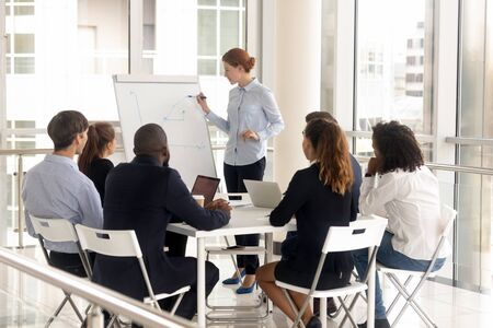 Foto de Young female employee with flip chart at presentation. Woman leader consulting diverse group at meeting room, boss mentor coach holds briefing at negotiation, corporate colleague training at boardroom - Imagen libre de derechos