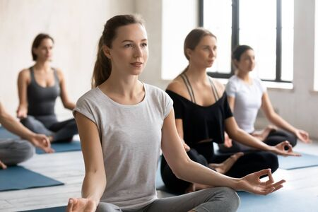 Photo pour Female yoga instructor and young like-minded group of people wearing comfy sportswear sitting in lotus position do meditation practice calming mind relaxing after work out during yoga session concept - image libre de droit