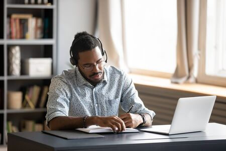 Photo pour Concentrated millennial african american guy wearing earphones, listening to favorite music while planning workday. Focused young biracial businessman watching educational lecture. writing down notes. - image libre de droit