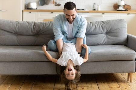 Photo pour Overjoyed loving young father sit on couch in kitchen feel playful have fun with cute little daughter, happy dad play engaged in funny activity with small girl child enjoy family weekend at home - image libre de droit