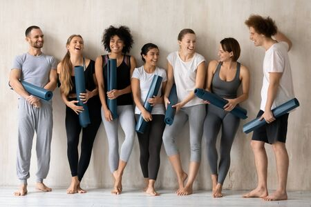 Yoga instructors of sport club after work out posing leaned on wall holding personal carpets. Like-minded multi-ethnic people wear comfy stylish activewear laughing enjoy talk ready for group class