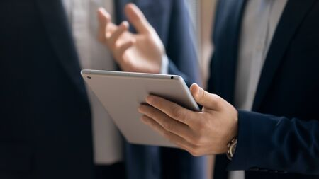 Photo for Close up of confident successful businessman hold modern tablet gadget discuss business project with colleague, concentrated male boss using pad device, browsing wireless Internet, technology concept - Royalty Free Image