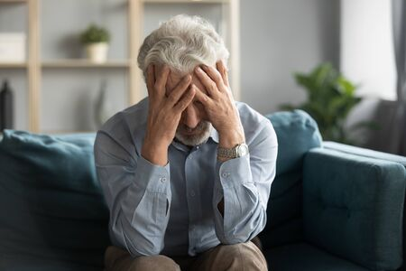 Depressed old 60s man sit on couch in living room feel lonely unhappy mourning yearning at home, stressed sad middle-aged retiree male lost in thoughts miss old times, elderly solitude concept