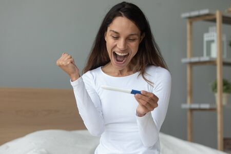 Overjoyed young woman sit on bed feel excited euphoric being pregnant, happy millennial girl look at pregnancy positive test results triumph with good news, infertility female problem concept