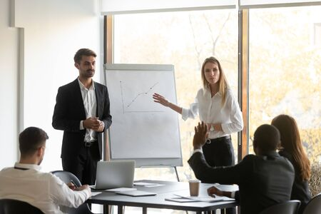 Photo pour Two young confident female and male speakers trainers holding educational seminar, standing near flipchart with graphs, answering to employees clients investors questions about growth strategy. - image libre de droit