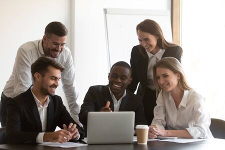 Photo pour Positive african american male employee showing computer software to happy diverse coworkers at meeting. Young mixed race smiling manager explaining project results to cheerful teammates at office. - image libre de droit