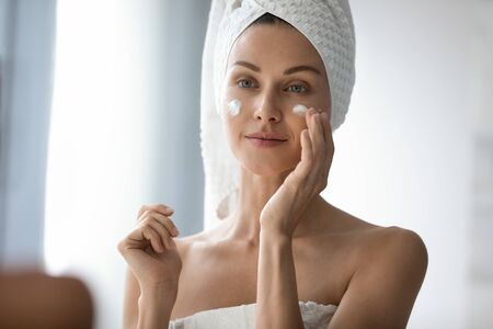 Photo for Head shot beautiful 30s lady looking in mirror, applying hydrating lotion creme on cheeks, finishing morning domestic skincare routine. Smiling woman grooming herself after showering in bathroom. - Royalty Free Image