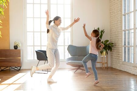 Foto de Full length excited young mommy repeating dance moves for school performance with happy small daughter. Joyful little preschool kid girl having fun together with cheerful mother in living room. - Imagen libre de derechos