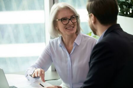 Foto de Smiling middle-aged female employee talk brainstorm with male colleague at office briefing in boardroom, happy diverse coworkers have fun laugh cooperating discussing ideas at meeting - Imagen libre de derechos