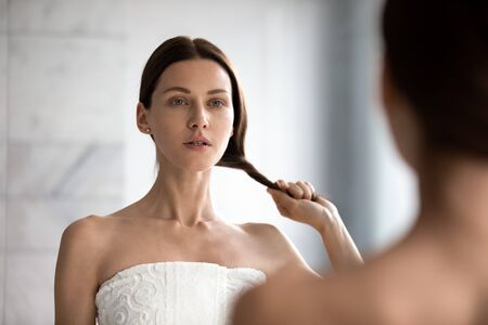 Photo pour Mirror reflection head shot peaceful young attractive brunette woman twisting long straight hair into bundle, doing hairstyle after morning shower in bathroom or checking dry ends, chevelure condition. - image libre de droit