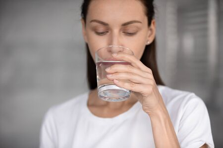 Photo pour Focus on peaceful young brunette woman drinking glass of fresh aqua, head shot close up. Attractive 30s lady sipping water, enjoying daily healthcare routine, every day healthy habit concept. - image libre de droit