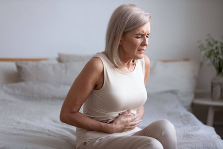 Photo pour Unhealthy middle aged frowning woman sitting on bed, putting hands on belly, suffering from strong stomach ache. Unhappy older lady having painful feeling in abdomen, pancreatitis gastritis symptom. - image libre de droit