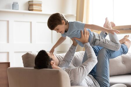 Photo for Happy young father relax in living room with small son playing together, overjoyed dad have fun hold fly with little preschooler boy child, enjoy weekend at home, parent kid relationship concept - Royalty Free Image