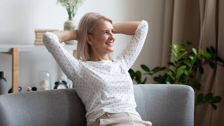 Photo for Pleasant smiling middle aged woman relaxing on cozy coach in modern living room, looking away. Happy older lady dreaming, visualizing future, resting, enjoying weekend free leisure time alone at home. - Royalty Free Image