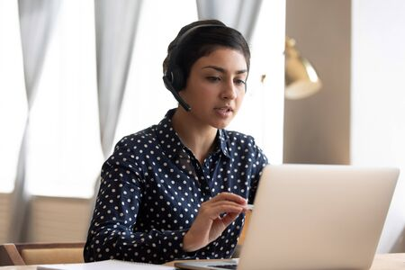 Photo pour Serious Indian woman wearing headphones with microphone talking, using laptop, looking at screen, young female consulting client, video call, student learning language online, listening lecture - image libre de droit