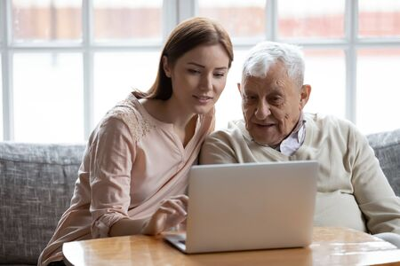 Photo pour Grown-up daughter and old 80s father choose goods or services via internet or web surfing together at home. Younger generation caring about older relatives teaching using computer useful apps concept - image libre de droit