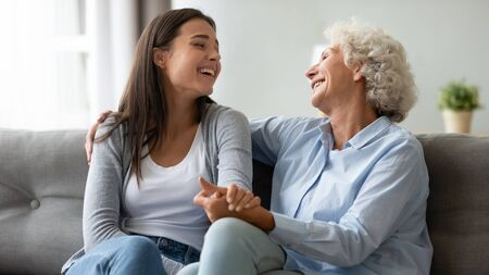 Photo pour Happy elderly mother and grown-up daughter sit on couch laugh talk and joke in living room, overjoyed millennial girl and elderly mom have fun relax enjoy family leisure weekend at home - image libre de droit