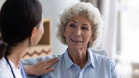 Foto de Attentive female caregiver visit positive senior old lady talking to retired lonely woman at home, caring doctor give help support consult mature grandmother, elderly healthcare concept - Imagen libre de derechos