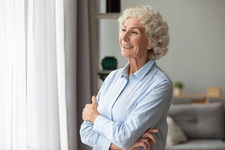 Happy elderly woman look in the window distance at home feel overjoyed excited about future, smiling mature female senior retired grandmother wait hope for the best to come, optimism concept
