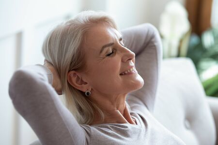 Photo for Smiling older woman relaxing with hands behind head on cozy sofa at home, happy sincere mature female with grey hair enjoying weekend, stretching on couch, resting and daydreaming, leaning back - Royalty Free Image