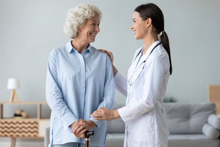Caring young nurse support visit positive senior grandmother with walking stick at home, attentive female caregiver or doctor give help assist old lady patient in retirement house or clinic