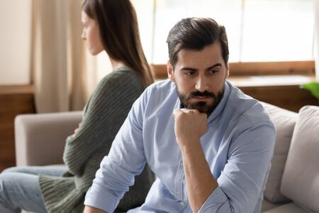 Photo pour Focus on stressed thoughtful young man sitting separate from offended wife on couch at home. Young frustrated married family couple ignoring each other after quarrel, relations problems concept. - image libre de droit