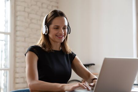 Photo pour Smiling woman wearing wireless headphones working typing on notebook sit at desk in office workplace. Enjoy e-learning process, easy comfortable application usage, listen music during workday concept - image libre de droit