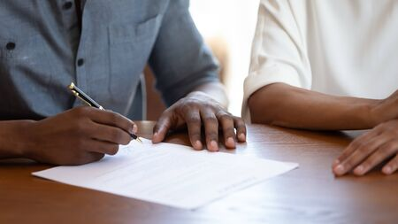 Horizontal image man holding pen put signature on agreement African couple filling form bank application taking loan, affirming rental contract, real estate purchasing, hands and table close up view