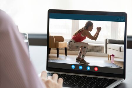 Photo pour Back view close up of woman watch online fitness training or course on laptop gadget at home, young female enjoy sports workout practice using wireless internet connection on modern computer - image libre de droit