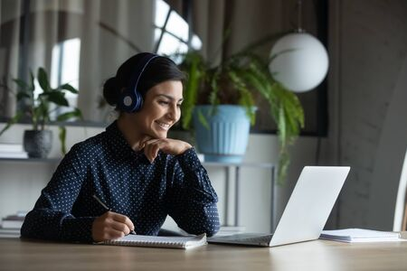Foto de Happy young indian girl with wireless headphones looking at laptop screen, reading listening online courses, studying remotely from home due to pandemic corona virus world outbreak, quarantine time. - Imagen libre de derechos
