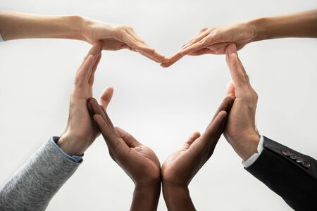 Photo pour Close up bottom view concept of diverse business people join hands forming heart. Show unity and support, protection of business. Multiracial colleagues involved in team building activity for charity. - image libre de droit