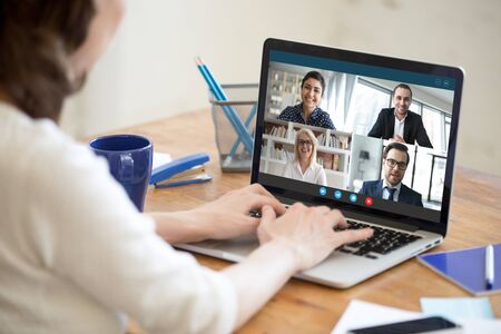 Foto de Diverse people take part in group video call pc screen cam app view over woman shoulder, seated at desk. Solve business issues distantly during coronavirus pandemic outbreak, videoconferencing concept - Imagen libre de derechos