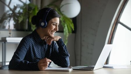 Photo pour Smiling Indian female employee in wireless earphones talk on video call, have web conference with colleagues, happy ethnic woman worker in headset watch webinar on modern laptop at home - image libre de droit
