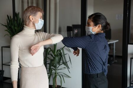 Photo pour Smiling diverse female colleagues wearing protective face masks greeting bumping elbows at workplace, happy coworkers in medical facial covers protect from COVID-19 pandemics, healthcare concept - image libre de droit
